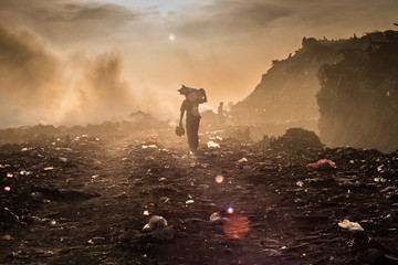 A waste picker is collecting reusable or recyclable materials in a open burning dump.