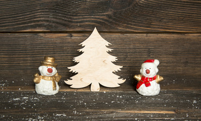 toy snowmen and wooden Christmas tree on a dark wooden backgroun