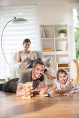 Cheerful family at home, Daddy playing with his daughter