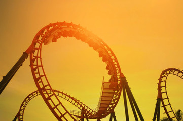 blurred Roller coaster ride in amusement park at evening
