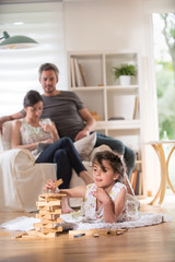 Cheerful family at home. little girl plays with a wooden game