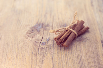 Cinnamon sticks close up on rustic wooden background