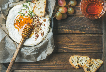 Homemade camembert cheese with honey, herbs and nuts, green grapes, baguette slices and glass of rose wine over rustic wooden background, top view, copy space
