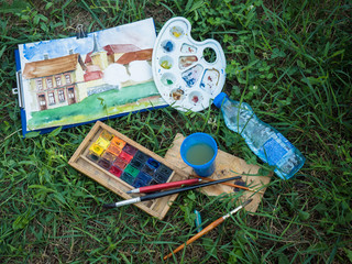 Picture of the used water colour paint with paintbrush laying on the green grass with cup of water and squeeze bottle near the ready picture