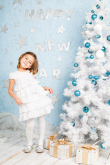 Smiling girl dancing nearly Christmas tree with Christmas decorations and presents