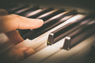 male musician fingers playing on piano keys