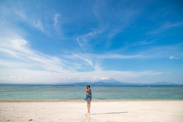 Happy girl jumping on the beach wit white sand. Tropical island Nusa Lembongan, Indonesia.