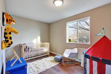 Nursery room interior with dark hardwood floor.