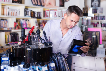 Man buying sex toys in shop