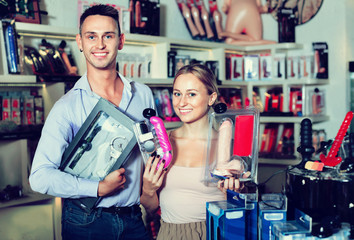 Young adult couple buying sex accessories
