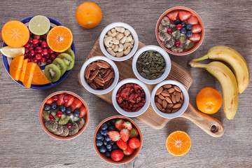 Smoothie  with fruits and berries on the grey wooden table, with variety of fruits and nuts around, selective focus; top view