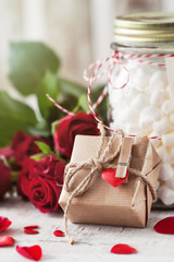 Small gift or present in natural paper with small heart and rose