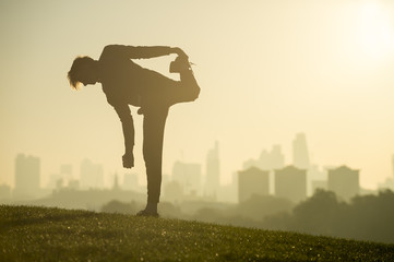 Silhouette of a man stretching on the grassy top of Primrose Hill in front of a misty golden sunrise view of the London city skyline