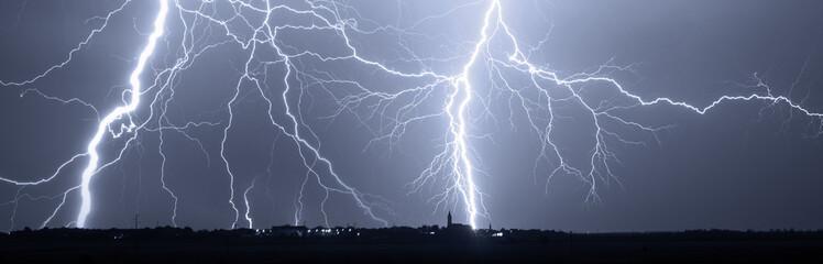 Fototapeta Thunder, lightnings and storm over city at night. obraz
