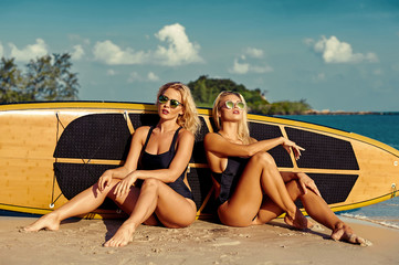 Sexy fit surfer girls posing near a surfboard on the beach