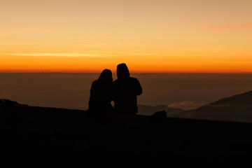 Silhouette couple lovers watching sunrise