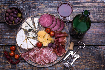 Red wine in a glass and a set of products - cheese, sausage, salami, olives, tomatoes, hot peppers, bread on a wooden board, background