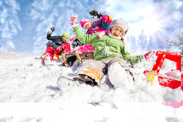 Happy children sledding at winter time. Group of children spendi