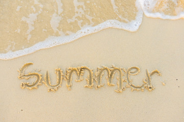 Summer text with white sandy beach and sea .