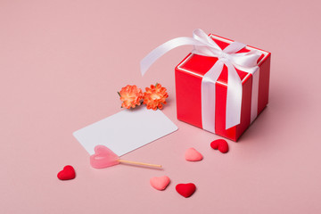 Valentine day composition: red gift box with bow, stationery / photo template, candy, spring flowers and small hearts on light pink background.