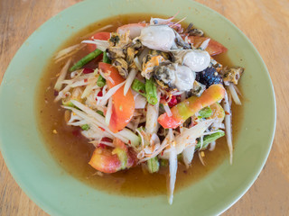 Papaya Salad (Som tum Thai) on wood table.
