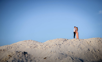 charming and young man and woman standing on sandy quarry