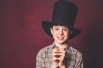 portrait, close up, children's emotions. Teen with a hat cylinder