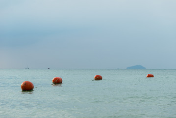 Red float, buoy in bay, gulf on sea, ocean with boat and island in background