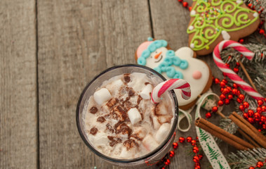 christmas background, composition. spruce branches, gingerbread (Snowman and Christmas tree), cocoa with cream and marshmallows, cinnamon, candy cane.