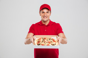 Young delivery man with pizza