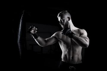 Male Athlete boxer punching a punching bag with dramatic edgy li