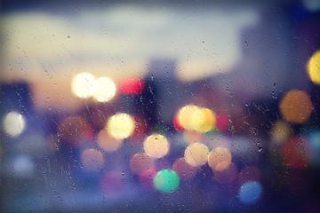 Glasscheibe mit Regentropfen in der Stadt - Buntes Bokeh am Abend