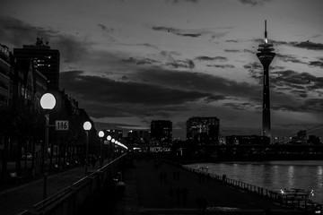 Beleuchtete Rheinkniebrücke in Düsseldorf an einem wolkenverhangenen Abend (schwarzweiß)