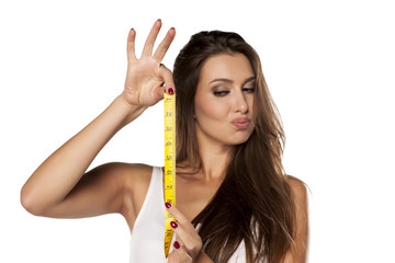 young woman is thrilled from the length of measuring tape