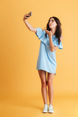 Portrait of a smiling woman making selfie photo on smartphone