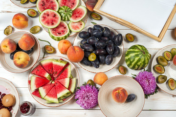 Colorful fruit set of purple, red and orange background in bowls. Plum, peaches, watermelon sliced above white tabletop