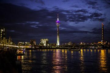 Beleuchtete Rheinkniebrücke in Düsseldorf an einem wolkenverhangenen Herbstabend