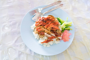 roasted duck in juicy sauce with rice, Steamed rice with roast duck on linoleum plate