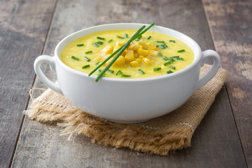 Corn soup in white bowl on wooden background.