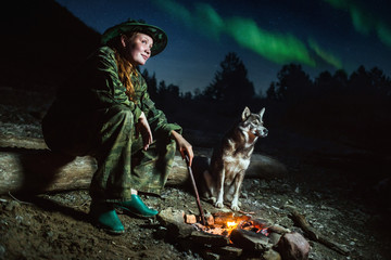 Tourist girl with her dog around campfire at misty landscape night stars and aurora borealis