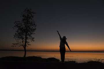 Silhouette of a beautiful woman wearing a hat spreading hand near big tree and reservoir, against sunset background.