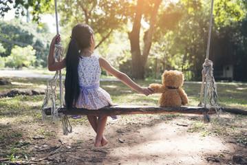 Cute little girl shook hands with a teddy bear on a wooden swing in park.