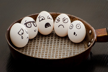Five eggs with painted emotions in a frying pan, a food concept