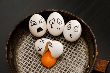 Top view of a broken egg, and egg with frightened faces in a frying pan. food concept