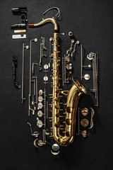 Tenor saxophone, exploded view drawing isolated on gray background.
