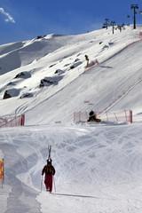 Skier ascend on snow ski slope at sun evening