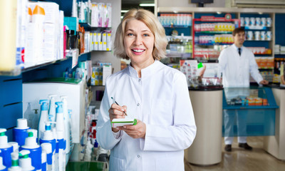 Portrait of two smiling pharmacists working in  farmacy