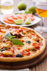 Big tasty pizza with seafood, tomatoes, wine on wooden table