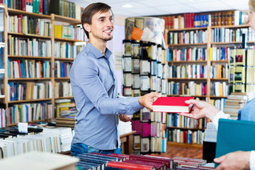 Young smiling man taking chosen book from seller