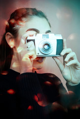 Beautiful girl with her vintage old retrò camera in a blurry red bokeh background